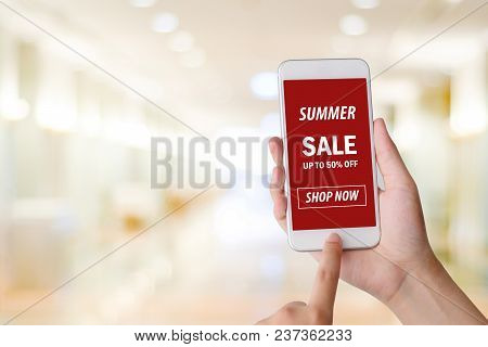 Hand Holding Smart Phone With Summer Sale Shopping Online Device On Screen Over Blue Background With