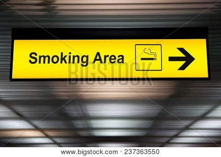 Smoking Area Sign With Icon And Arrow Pointing To Smoking Area Zone Hanging From Airport Ceiling At