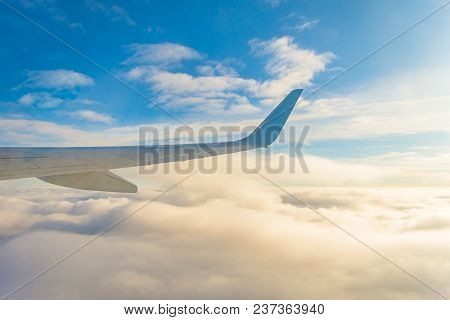Wing View Of The Airplane On A Winglets, Fluffy Clouds On The Skyline During Climbing Flight Level