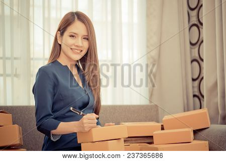 Woman Writing Address And Send Package For Online Business