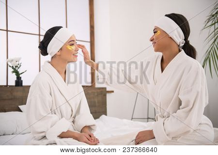 Same Sex Couple. Nice Pleasant Woman Looking At Her Partner While Helping Her To Wear Eye Patches