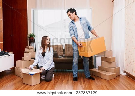 Happy Couple Packing Boxes And Moving Into New Home.moving House