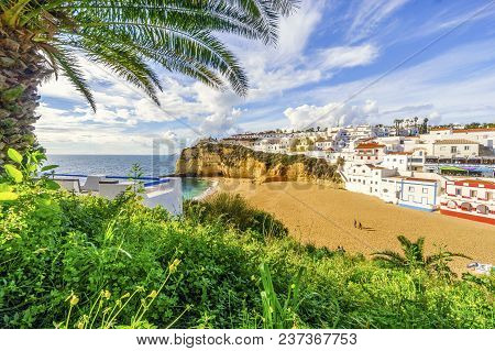 Sandy Beach Surrounded By Cliffs With Palm Trees In Carvoeiro, Algarve, Portugal