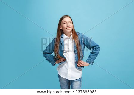Happy Teen Girl Standing, Smiling Isolated On Trendy Blue Studio Background. Beautiful Female Half-l