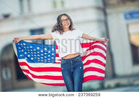 Happy Young American School Girl Holding And Waving In The City With Usa Flag
