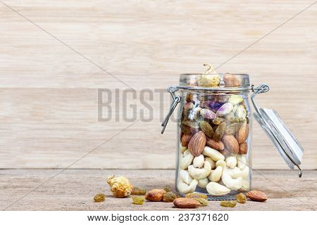 Dried Fruits And Variety Of Nuts Into A Bottle Glass On Wooden Background, Such As Figs, Almonds, Ra