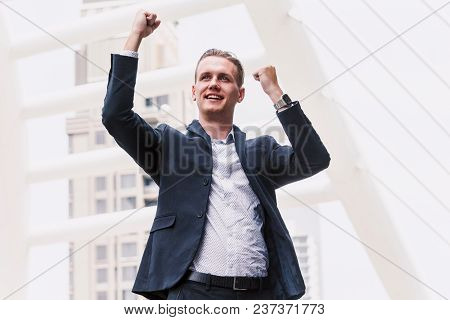 Successful Businessman Celebrating With Arms Up At Outdoor