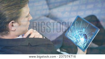 Digital composite of Businessman using digital tablet with overlay