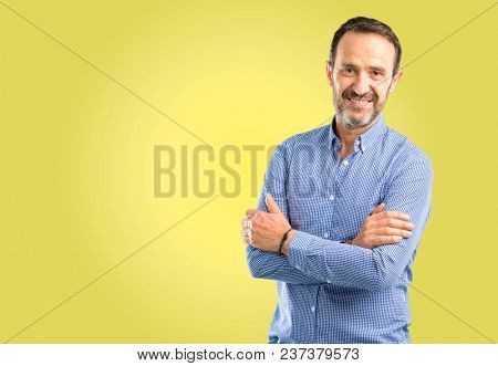 Handsome middle age man with crossed arms confident and happy with a big natural smile laughing