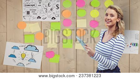 Digital composite of Businesswoman holding tablet PC with adhesive notes stuck on wall