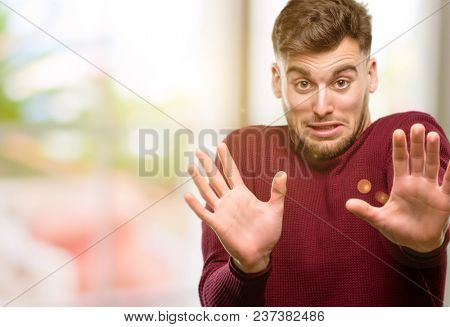 Handsome young man disgusted and angry, keeping hands in stop gesture, as a defense, shouting