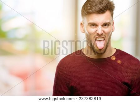 Handsome young man feeling disgusted with tongue out