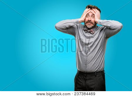 Middle age man, with beard and bow tie stressful keeping hands on head, terrified in panic, shouting