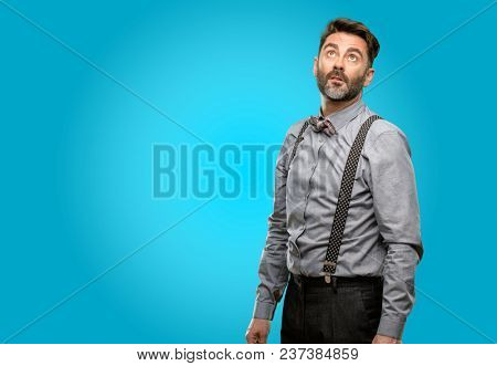 Middle age man, with beard and bow tie confident and happy with a big natural smile laughing looking up