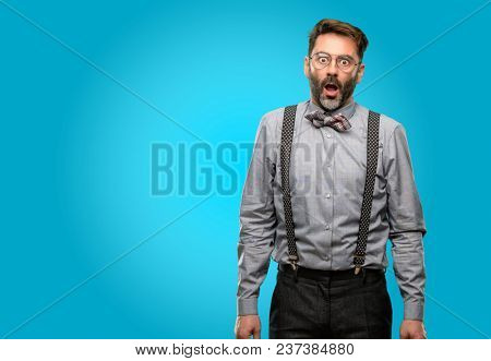 Middle age man, with beard and bow tie happy and surprised cheering expressing wow gesture