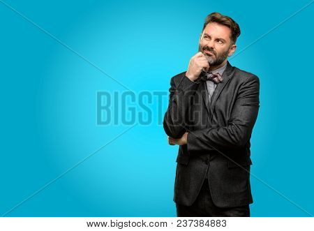 Middle age man, with beard and bow tie thinking thoughtful with smart face