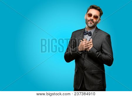 Middle age man, with beard and bow tie with hands in heart, expressing love and health concept