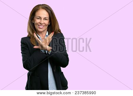 Middle age business woman annoyed with bad attitude making stop sign crossing hands, saying no, expressing security, defense or restriction