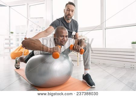 Physical Activity. Serious Professional Trainer Looking At His Client While Monitoring How He Does P