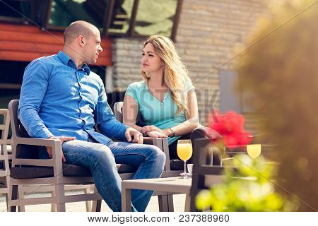 Flirting In A Cafe. Beautiful Loving Couple Sitting In A Cafe Enjoying In Coffee And Conversation. L