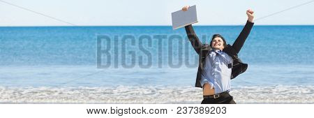 Business man with laptop celebrating against blurry horizon