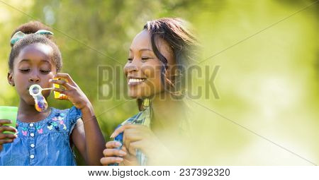 Mother and daughter blowing bubbles with blurry green transition