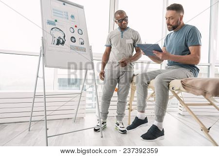 Medical Diagnosis. Nice Bearded Man Reading His Diagnosis And Asking A Question To His Therapist