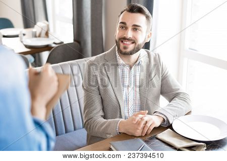 Happy Positive Handsome Young Businessman Sitting At Table With Plate And Smiling To Waitress While