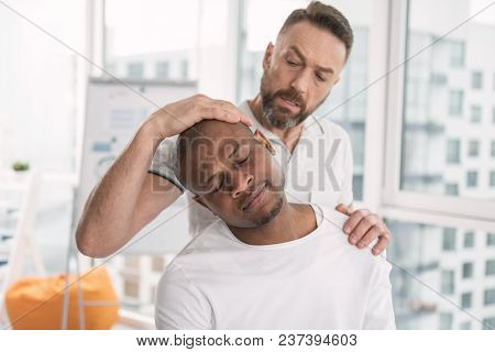 My Shoulder. Nice Young Man Turning His Head While Showing His Shoulder To The Doctor