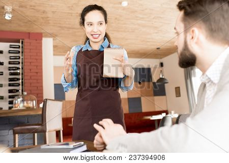 Cheerful Content Beautiful Young Hispanic Waitress In Apron Holding Sketchpad Gesturing While Explai