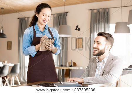 Cheerful Positive Attractive Young African-american Waitress In Apron Talking To Happy Customer And