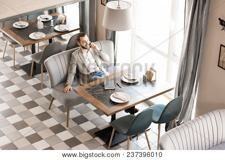 Happy Positive Handsome Young Businessman In Casual Clothing Sitting On Comfortable Sofa And Talking