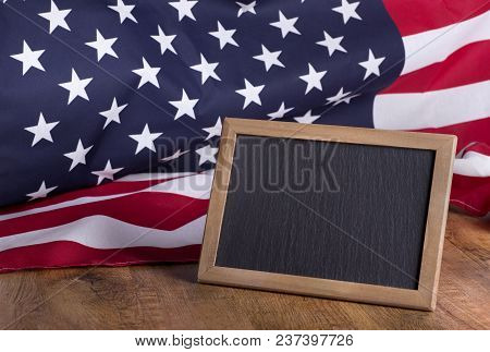 Blank Chalkboard For Copy Space With American Flag In Background On A Rustic Wood Surface