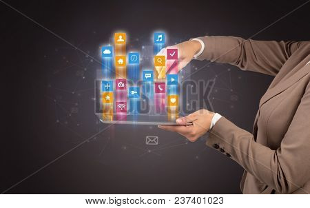 Female elegant hand holding tablet with colourful application icons