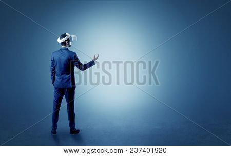 Businessman wearing vj glasse in an empty room with no wallpaper