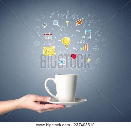 Young female hand holding tea mug with colorful communication related drawings above it