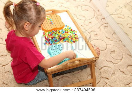 The Child Collects The Puzzle Sitting At The Table At Home. Development Of Fine Motor Skills