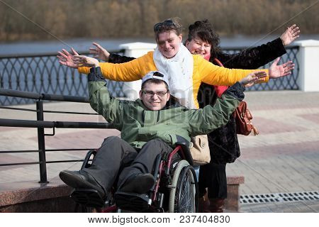 Belarus, Gomel, On April 11, 2018. City Day. Central Park.disabled In A Wheelchair With Family In Th