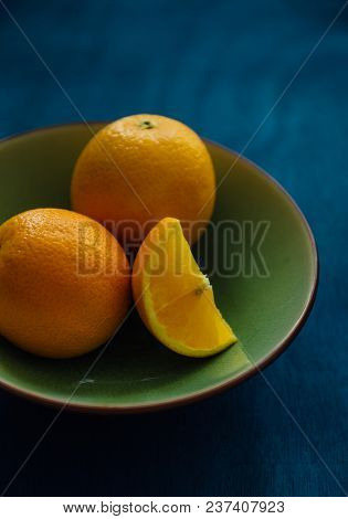 A piece of sliced orange fruit is placed in a bowl along with whole oranges. Bowl of fresh and juicy tangerines.