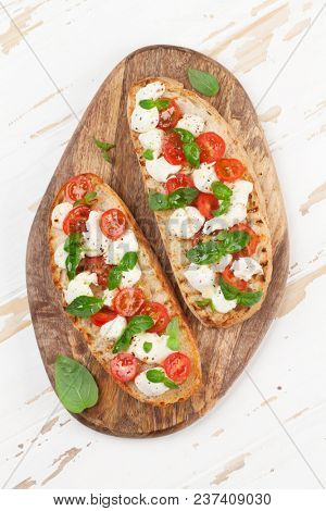 Caprese bruschetta toasts with mozzarella, cherry tomatoes and fresh garden basil. Top view