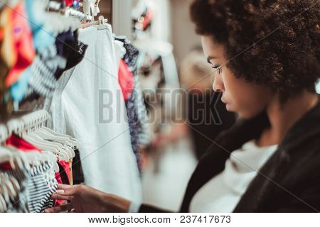 True Tilt-shift View Of A Young African-american Girl In A Shop Choosing Clothes For Herself; The Bl