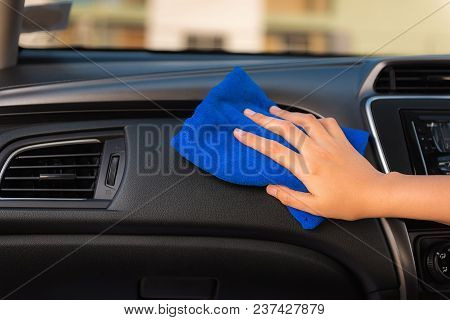 Close-up Portrait Of A Driver Woman Cleaning Cconsole Her Car With Microfiber Towel.