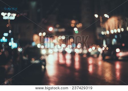 Blurred City At Night. Bokeh. Beautiful Abstract Background With Defocused Buildings, Cars, City Lig