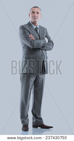 Mature business man arms folded isolated on gray.