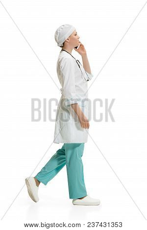 Beautiful Young Woman In White Coat Going At Studio With Mobile Phone. Full Length Shot Isolated On