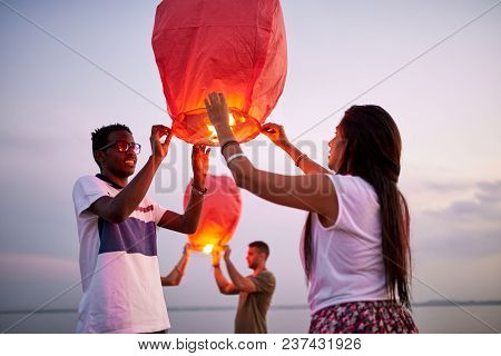 Happy Positive Young Multiethnic Couple Preparing To Launch Sky Paper Lantern While Standing On Beac