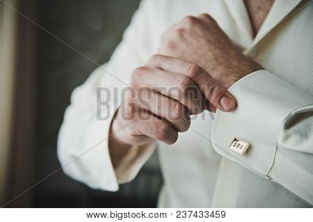 Putting On The Clasps On The Sleeve Of A Shirt.