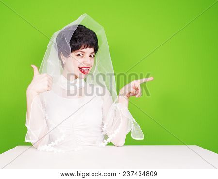 Caucasian Fiancee In White Dress Pointing To The Side. Young Fiance Sitting At A White Table Pointin