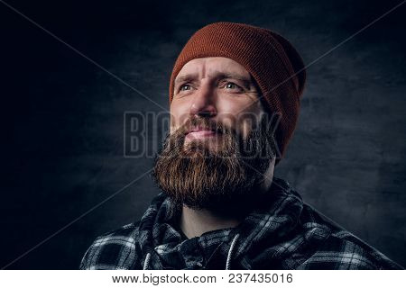 Portrait Of Bearded Male In A Hat And Fleece Shirt Over Dark Grey Background.