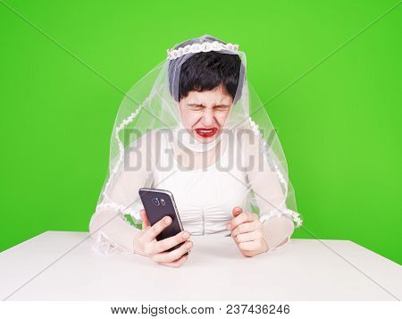 Wedding Relationship Difficulties. Sad Woman With A Phone In Her Hand Is Crying. Unhappy Bride Cryin